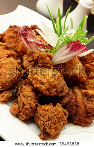 Crispy fried chicken served with garnishing. - stock photo