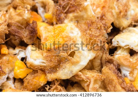 Crispy fried egg , cut into small pieces . - stock photo