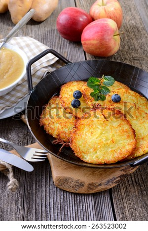 Crispy fried homemade potato pancakes served in an iron pan with apple sauce