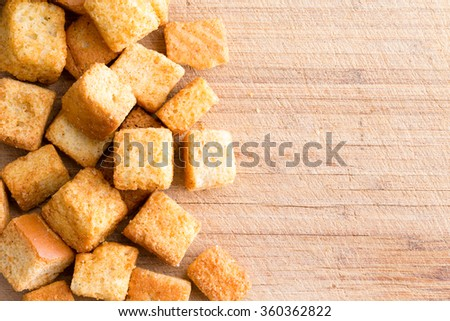 Crispy golden freshly sauteed croutons made of cubed white bread as a delicious crunchy addition to a bowl of hot winter soup, overhead on wood with copy space - stock photo