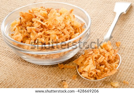 crispy onion in a glass bowl and spoon on jute - stock photo