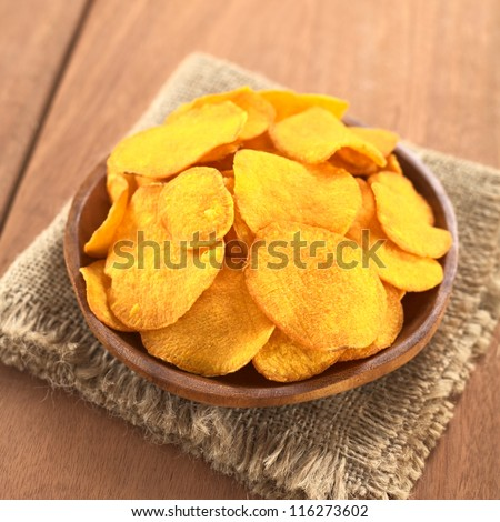 Crispy Peruvian sweet potato chips on wooden plate (Selective Focus, Focus on the lower part of the sweet potato chips) - stock photo