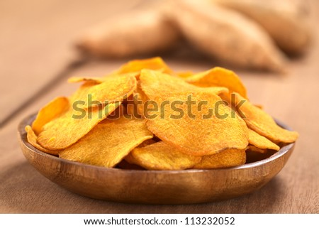 Crispy Peruvian sweet potato chips on wooden plate with sweet potatoes in the back (Selective Focus, Focus on the middle of the sweet potato chip in the front) - stock photo