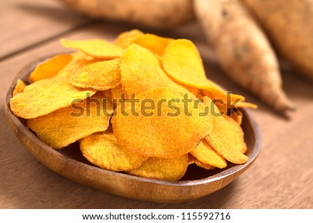 Crispy Peruvian sweet potato chips on wooden plate with sweet potatoes in the back (Selective Focus, Focus one third into the sweet potato chips) - stock photo