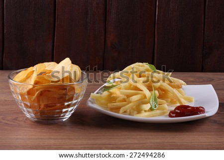 Crispy potato chips. The fries on the table. Potatoes fried with herbs and spicy sauce. Unhealthy food.  - stock photo