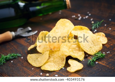 Crispy potato chips with dill and beer bottle - stock photo