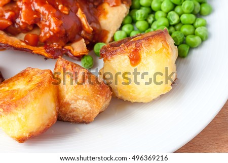 Crispy roast potatoes on the side of a dinner plate
