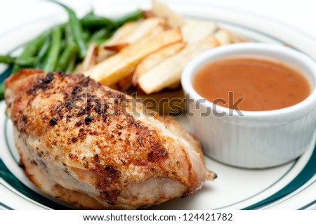 crispy skinned roast chicken breast with dipping sauce, hand cut french fries and green beans - stock photo