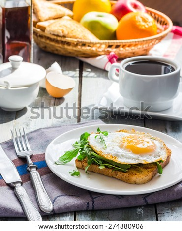 crispy toast with a fried egg and green arugula, coffee cup, fruit, breakfast on the wooden background - stock photo