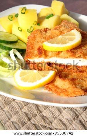 Crispy Vienna schnitzel with potatoes and salad - stock photo