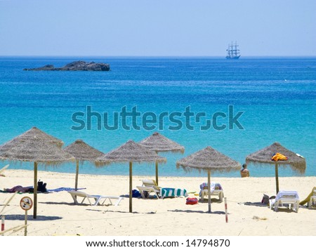 cristal clear waters, with classic sail boat, in sagres beach in the algarve, portugal - stock photo