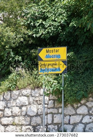 CROATIA -CIRCA JULY 2014- A road sign marks the direction of the towns of Mostar, in Bosnia, and Dubrovnik, in Croatia (both former Yugoslavia). The writing in Cyrillic alphabet is crossed out.