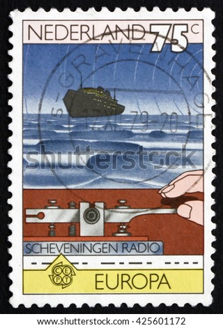CROATIA ZAGREB, 9 OCTOBER 2015: a stamp printed in Netherlands shows Hand on Morse Key, and Ship at Sea, circa 1979 - stock photo