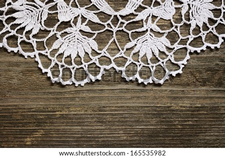 Crochet lace on a gray weathered wood - stock photo