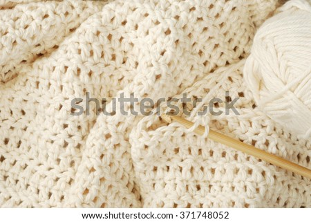 Crochet project - partially finished.  Natural, pure, organic cotton yarn being worked into a pattern of double crochet stitches using a bamboo hook. - stock photo