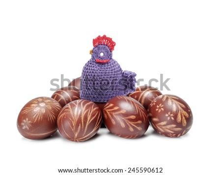 Crochet sitter sitting on pile of easter eggs shot on white - stock photo
