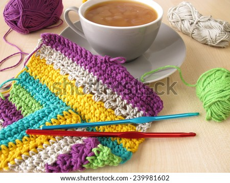 Crochet work and a cup of coffee with milk - stock photo
