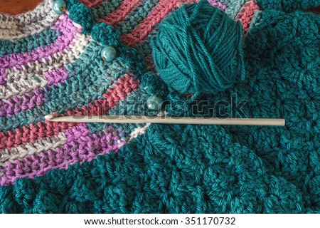 Crocheted baby sweater with a crochet hook and ball of yarn. - stock photo