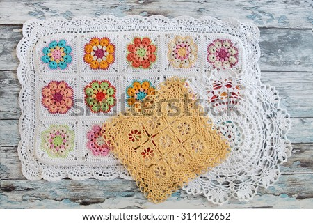 crocheted lace on wooden background - stock photo