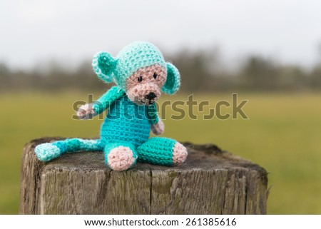 crocheted selfmade monkey toy sitting on fence outdoor - stock photo