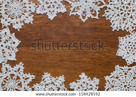 Crocheted snowflakes  on a wooden background - stock photo