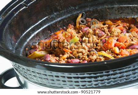 Crock pot with delicious home made chili simmering. - stock photo