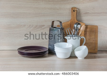 Crockery, tableware, utensils and other different stuff on wooden table-top. Kitchen still life as background for design. Image with copy space.