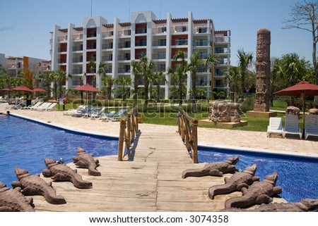 Crocodile statues flank a wooden bridge in an El Salvador resort - stock photo