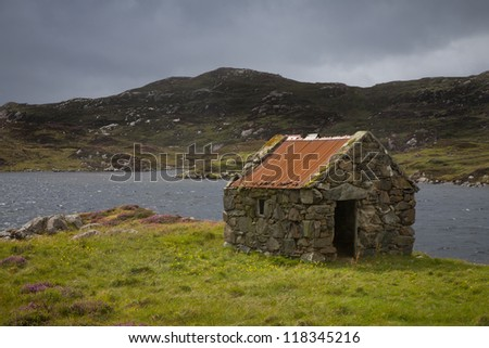 Crofters Hut next to a Loch in the Outer Hebrides - stock photo