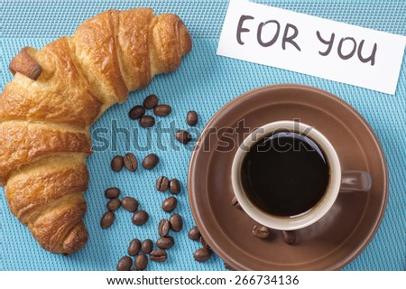 """Croissant and a cup of strong black coffee. Cup of coffee and a bun. Breakfast treat. Breakfast croissant and coffee. Note """"For You"""", a surprise. French breakfast. Restaurant, cafeteria. Top view. - stock photo"""
