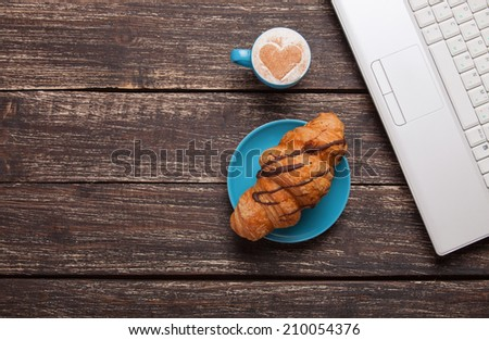 Croissant and cup of coffee with laptop on wooden table. - stock photo