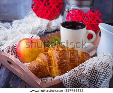 Croissant, coffee and heart on wooden background. Selective focus
