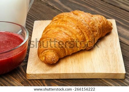 Croissant, jam and milk close up. - stock photo