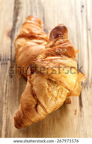 croissant on wooden background - stock photo