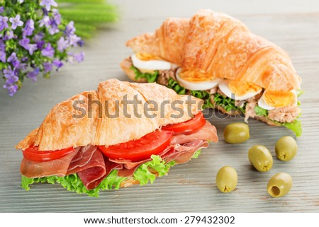 croissant sandwiches and green olives on wooden table - stock photo