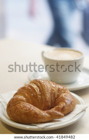 Croissant with Cappuccino on the background. Shallow deep of field, focus on croissant.