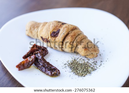 Croissant with dried tomatoes and spice - stock photo