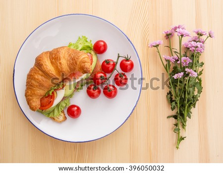 Croissant with fish, tomatoes and lettuce - stock photo