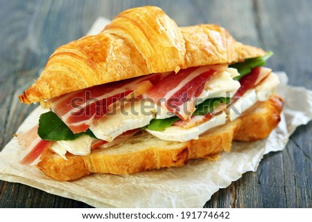 Croissant with ham and brie cheese on white parchment. - stock photo