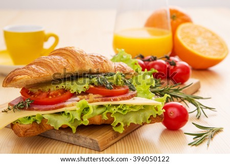 Croissant with ham, cheese, lettuce and tomato