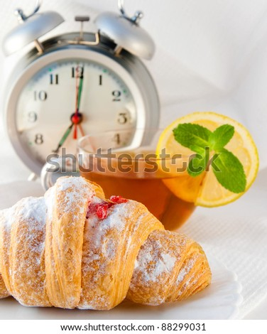 Croissant with jam and tea with a lemon and an alarm clock, a light morning meal - stock photo