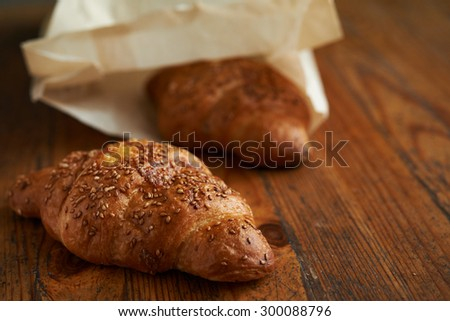 croissant with sesame  on wooden background - stock photo