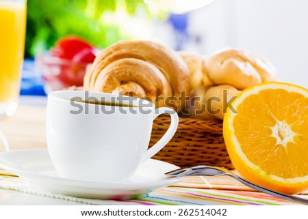 Croissants and cup of coffee on breakfast table - stock photo