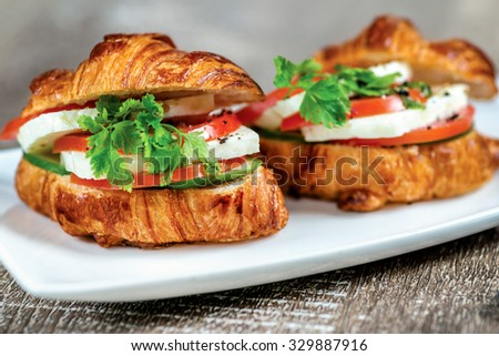 Croissants with cheese feta and mozzarella, pesto and roasted zucchini and bell pepper. - stock photo