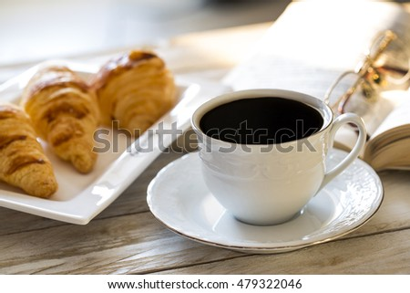 Croissants with coffee on the wooden table