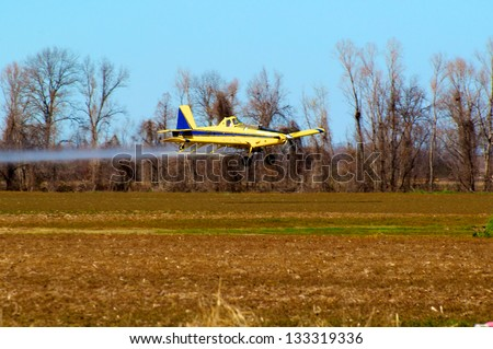 Crop duster at work applying chemicals to field - stock photo
