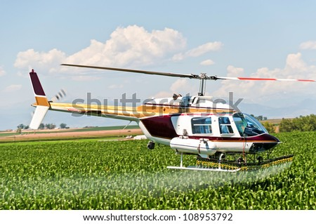 Crop duster helicopter spraying pesticide on a cornfield in central Colorado with the Rocky Mountains in the background. - stock photo