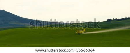 Crop dusting airplane spraying pesticide on wheat fields in the Palousezfz - stock photo