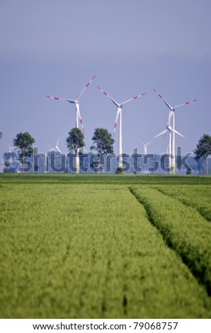 crop fields with wind power stations in the background - stock photo