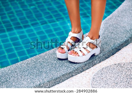 Crop photos. Female feet in white sandals with heels. It stands on the edge of the pool with blue water. Stylish image of trendy silver summer sandals. - stock photo